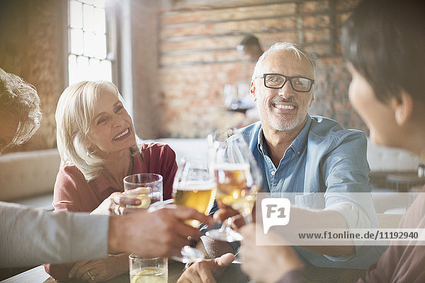 Couples toasting beer and wine glasses at restaurant table