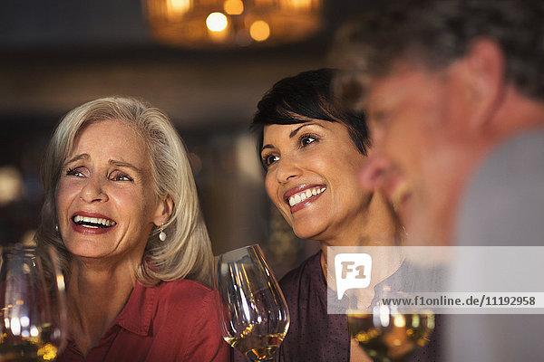 Smiling women drinking white wine at bar