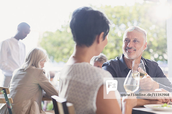 Couple talking and drinking white wine at outdoor restaurant table