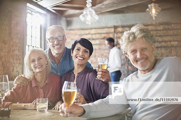 Portrait smiling couples drinking beer at restaurant table