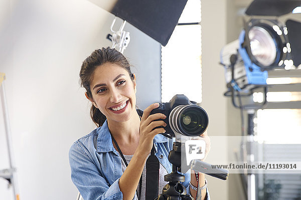 Smiling female photographer behind camera in studio