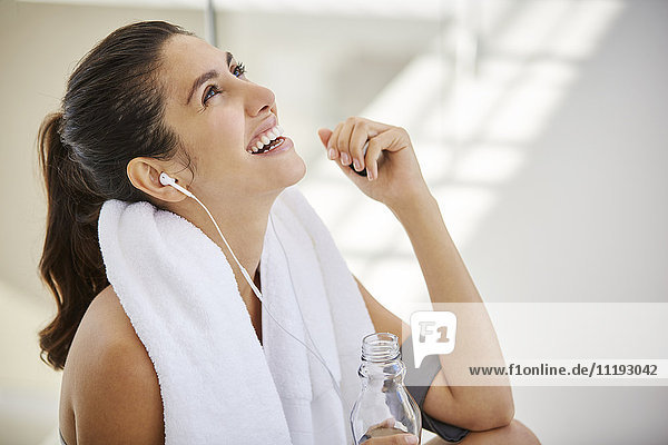 Laughing woman listening to music with headphones resting post workout
