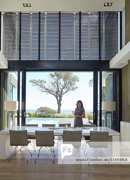 Businesswoman working at dining table in luxury home showcase interior