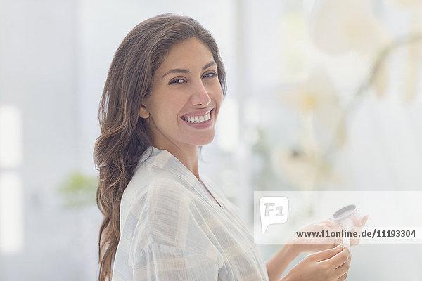 Portrait smiling brunette woman applying makeup