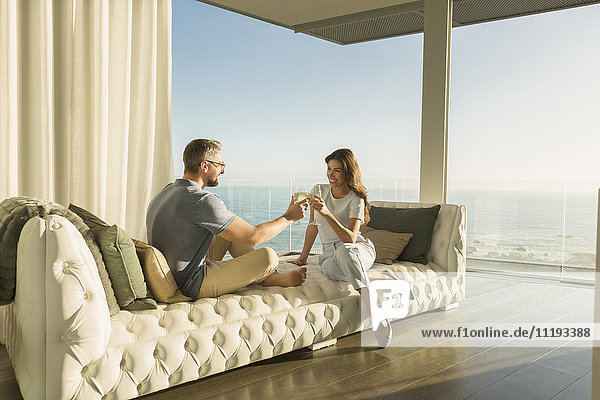 Couple toasting wine glasses on luxury tufted chaise lounge with ocean view