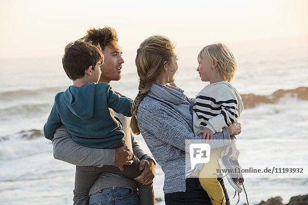 Fröhliche junge Familie am Strand bei Sonnenuntergang