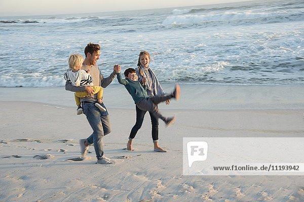 Fröhliche junge Familie mit Spaß am Strand bei Sonnenuntergang