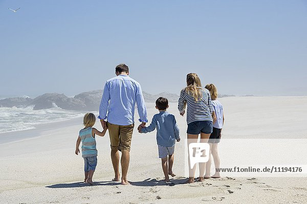 Rückansicht einer fünfköpfigen Familie beim Spaziergang am Strand