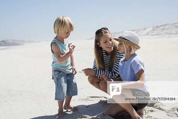 Schöne Frau genießt mit ihren Kindern am Strand