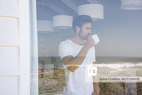Young man looking through window with cup of coffee