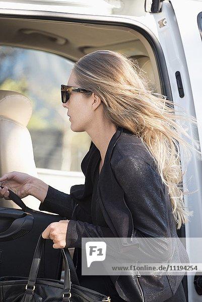 Schöne Frau mit Gepäck im Auto