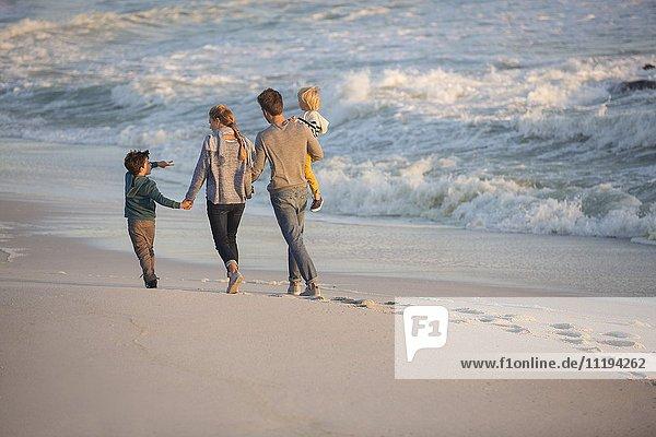 Rückansicht einer Familie beim Spaziergang am Strand
