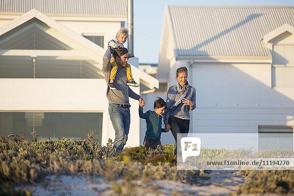 Glückliche Familie beim Spaziergang vor einem Haus