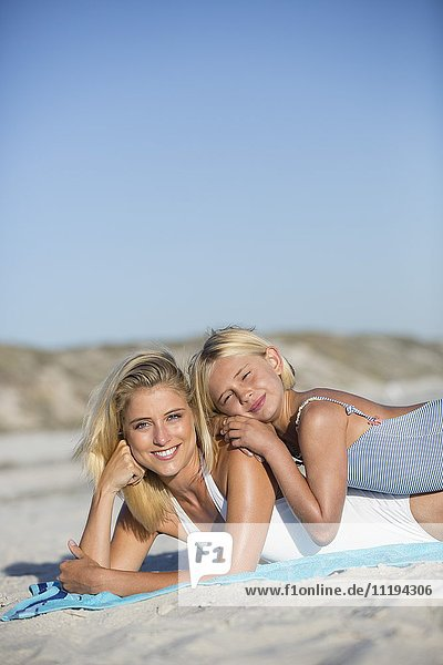 Portrait of a happy woman and her daughter lying on the beach