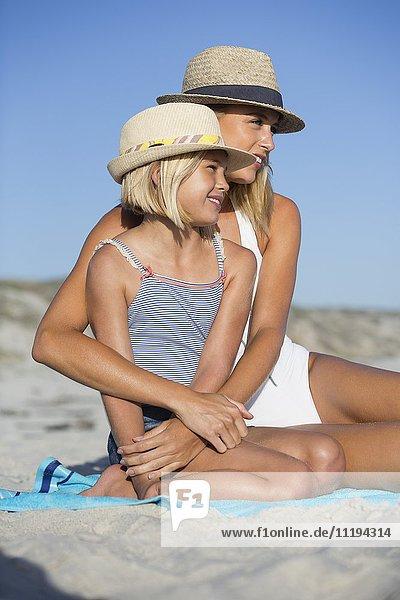 Nahaufnahme eines Mädchens  das mit seiner Mutter am Strand sitzt.