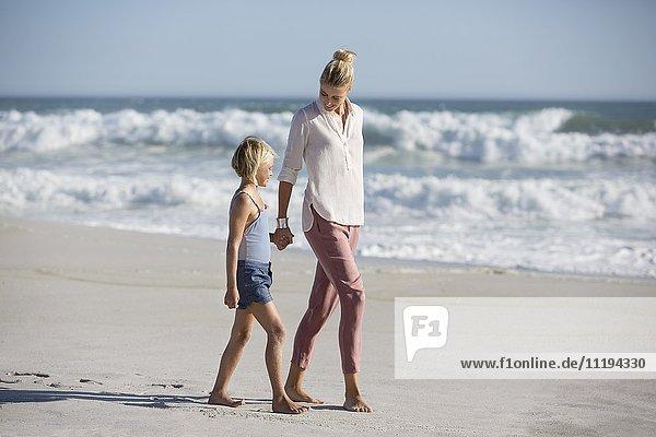 Profil einer Frau mit ihrer Tochter  die am Strand spazieren geht