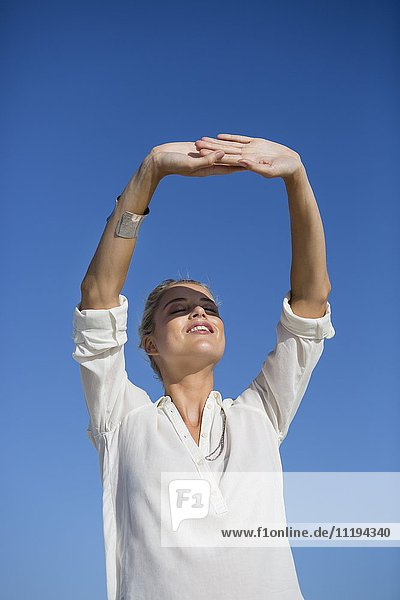 Young woman standing with her eyes closed against blue sky