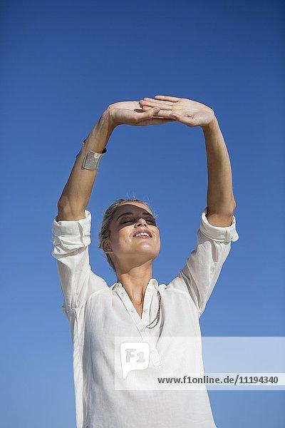 Junge Frau steht mit geschlossenen Augen vor blauem Himmel