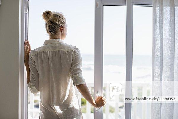 Junge Frau steht am Fenster zu Hause