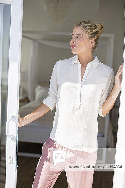 Fröhliche junge Frau steht am Fenster