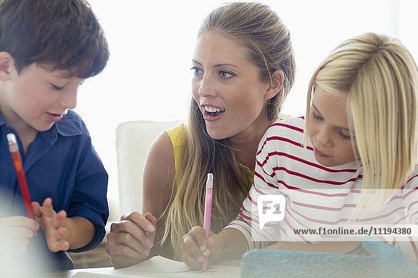 Glückliche Frau unterrichtet ihre Kinder zu Hause