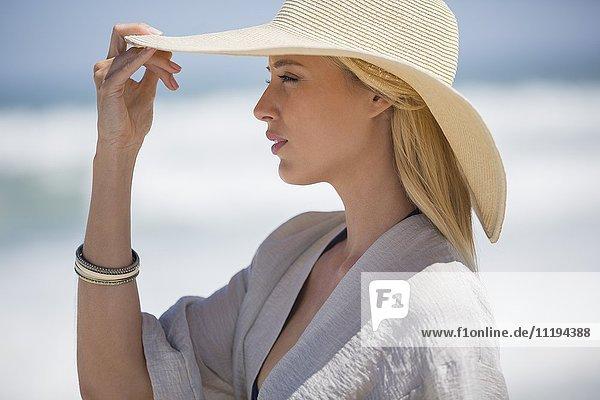 Schöne junge Frau mit Sonnenhut am Strand