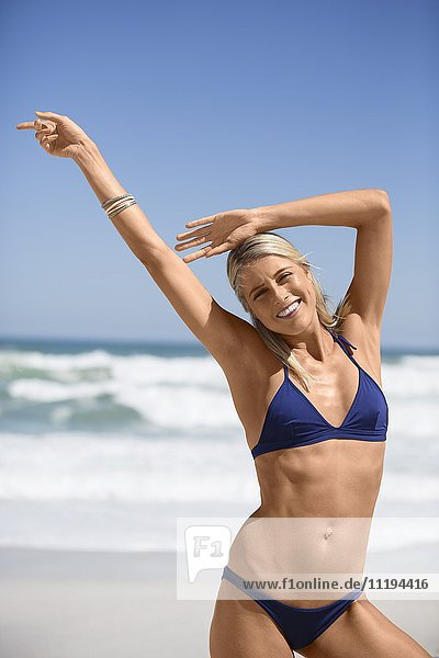 Porträt einer glücklichen Frau  die am Strand lächelt