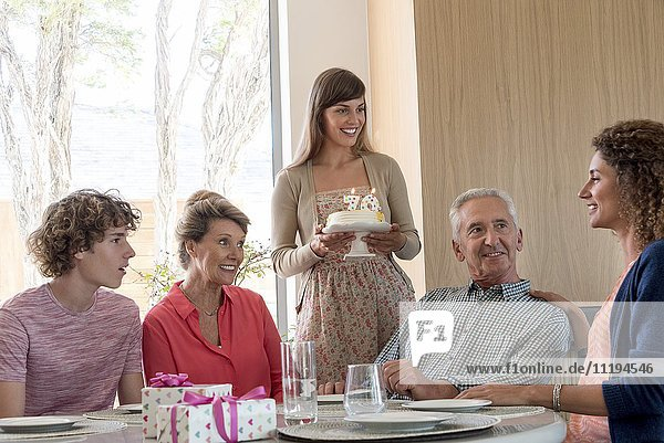 Glückliche Großeltern feiern Geburtstag mit Enkelkindern zu Hause