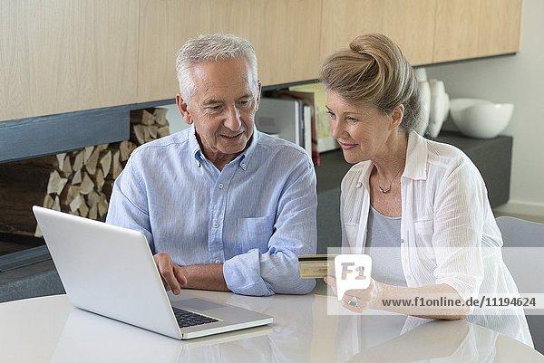 Senior Paar online einkaufen mit Laptop zu Hause