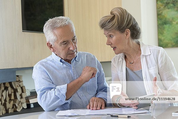 Senior couple sorting bills at home