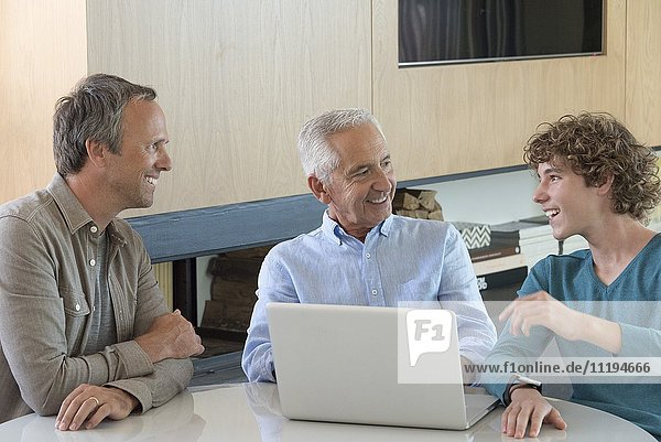 Happy senior man using a laptop with son and grandson in a living room
