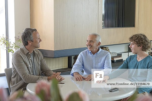 Glücklicher Senior im Gespräch mit Sohn und Enkel im Wohnzimmer