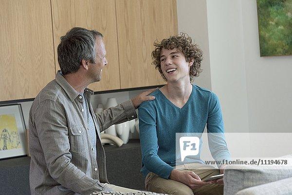 Glücklicher Vater und Sohn reden im Wohnzimmer