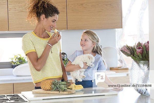 Kleines Mädchen und ihre Mutter essen Ananas in der Küche