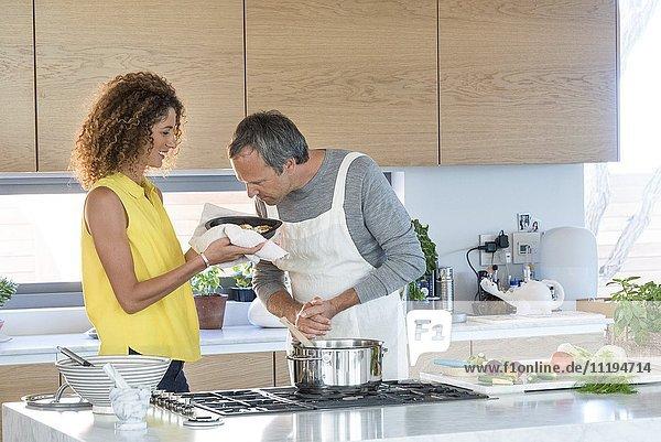 Ein reifer Mann  der das Essen riecht  das seine Frau in der Hand hält.
