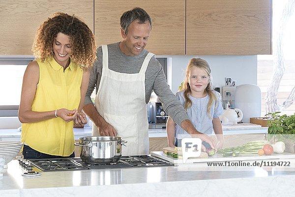 Kleines Mädchen mit Eltern bei der Zubereitung des Essens in der Küche