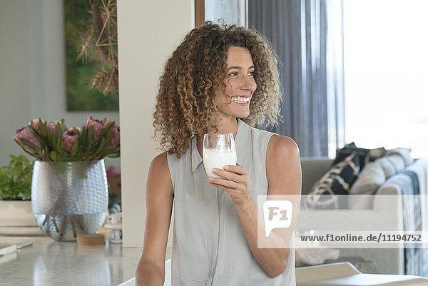 Nahaufnahme einer fröhlich schönen Frau beim Milchtrinken