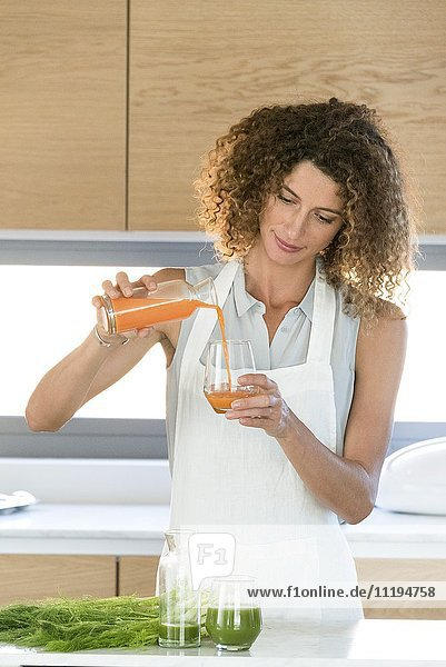 Frau gießt Gemüsesaft in ein Glas