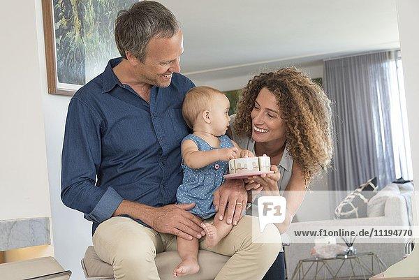 Glückliche Frau  die ihrer kleinen Tochter  die auf dem Schoß ihres Vaters sitzt  Spielzeug schenkt.