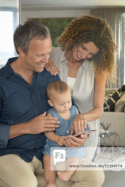 Glückliches Paar zeigt Bilderbuch für seine kleine Tochter
