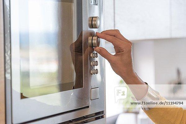 Nahaufnahme einer Frauenhand im Ofen
