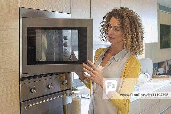 Nahaufnahme einer Frau beim Blick in den Ofen