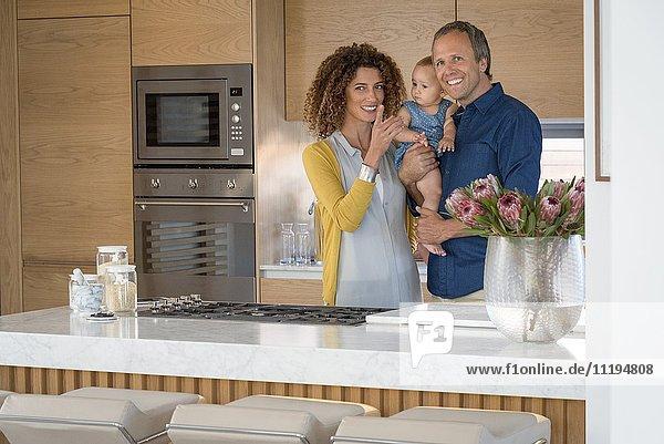 Ein glückliches Paar steht mit seiner Tochter in der Küche.