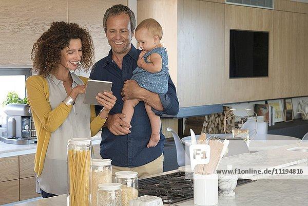 Paar mit digitalem Tablett mit ihrer Tochter in der Küche