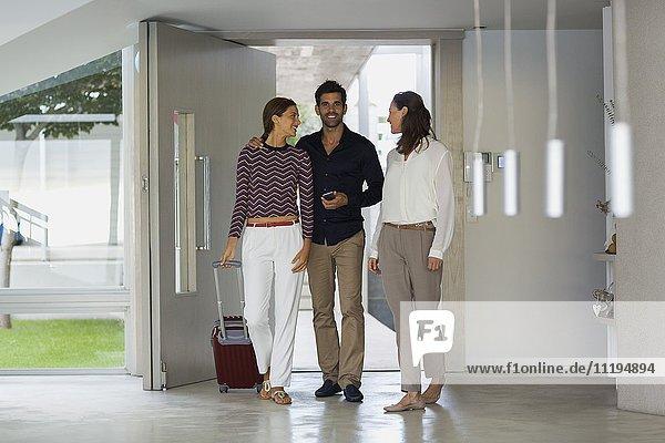 Fröhliche Frau begrüßt ihre Freunde am Eingang