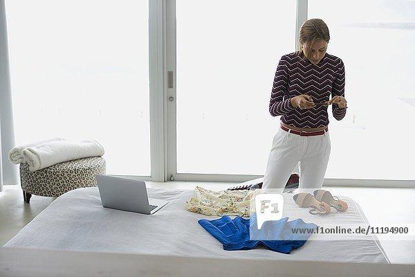 Junge Frau mit einem Smartphone im Schlafzimmer