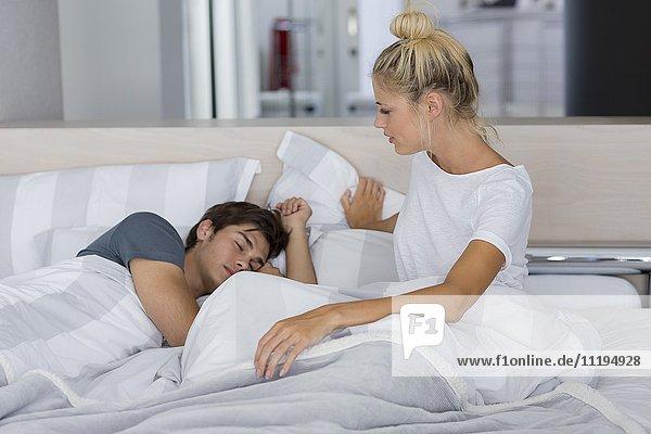 Frau schaut ihren Mann an  der auf dem Bett schläft.