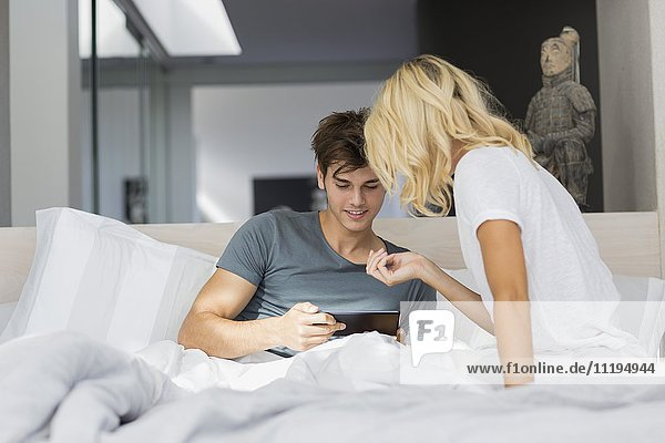 Couple using a digital tablet on the bed