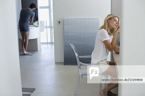 Junge Frau schminkt ihr Gesicht mit ihrem Mann im Hintergrund