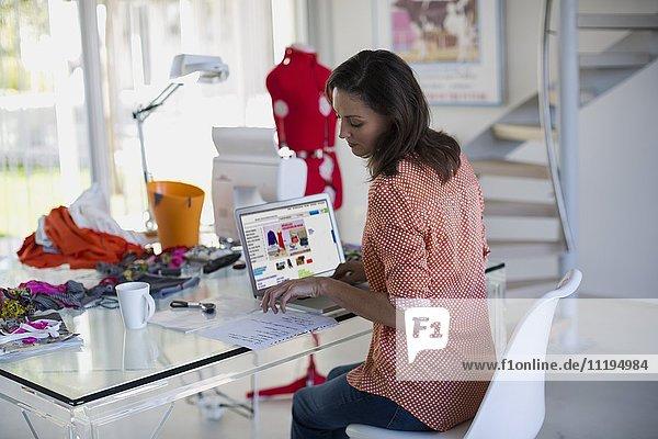 Modedesignerin bei der Arbeit am Laptop in ihrem Büro